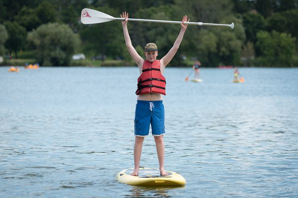 An AYA member standing on a paddle board in the middle of a lake, raising his paddle over his head