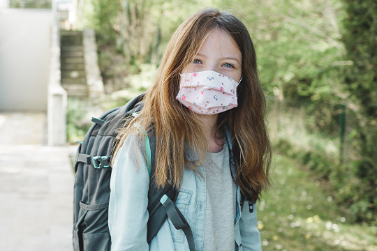 School-age girl wearing a face mask and backpack before school