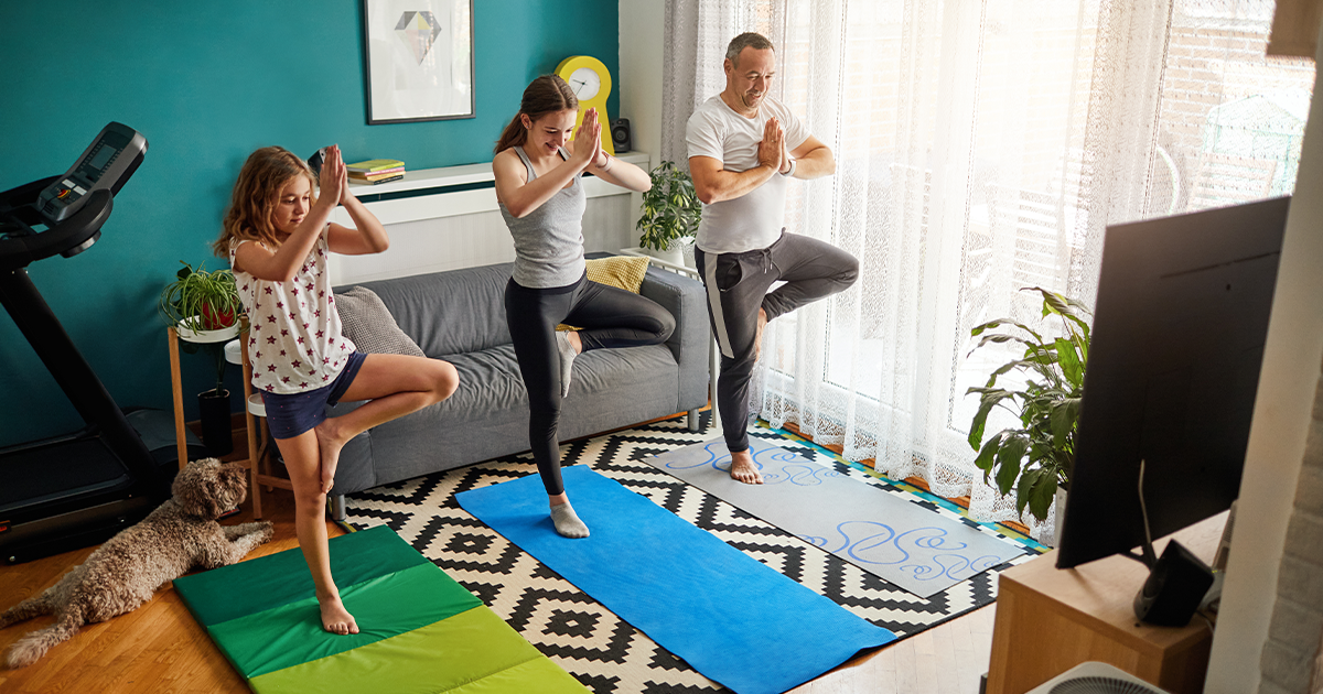 Father and his two teenage daughters doing yoga at home