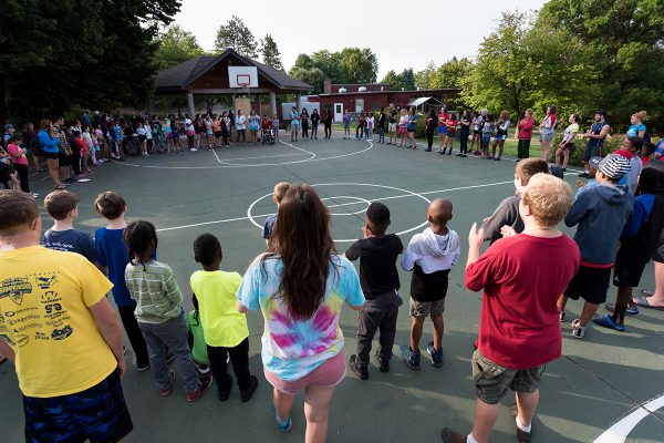 Campers form a circle around the basketball court at camp VIP