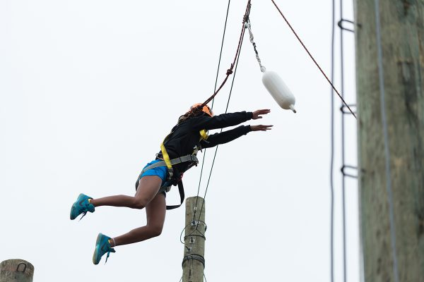 An airborne camper jumps off a platform in the ropes course