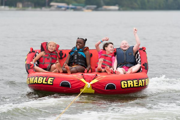 Four campers are pulled behind a boat on a an inflatable raft