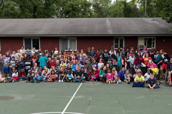 All camp staff and campers pose in front of a building