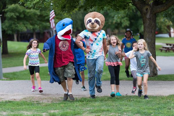 Staff in costume are chased by young campers during a game