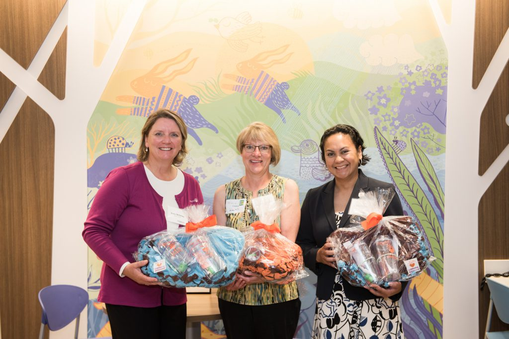 Soja Mehring and Liwang Ojala deliver care packages to patient families; holding care packages