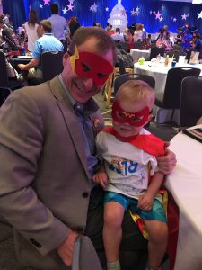 A young boy in a red superhero mask is on the lap of a man in a suit and a superhero mask