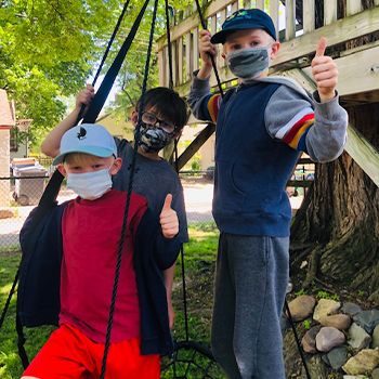 Three boys play outside with camouflage patterned face masks