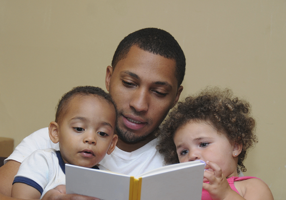 Father reading to young son and daughter