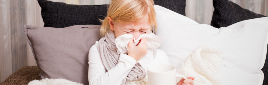 Child sneezing and blowing into tissue, sick, on couch