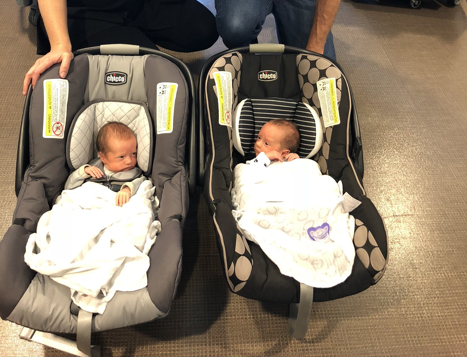 Twins heading home from the NICU in car seats.