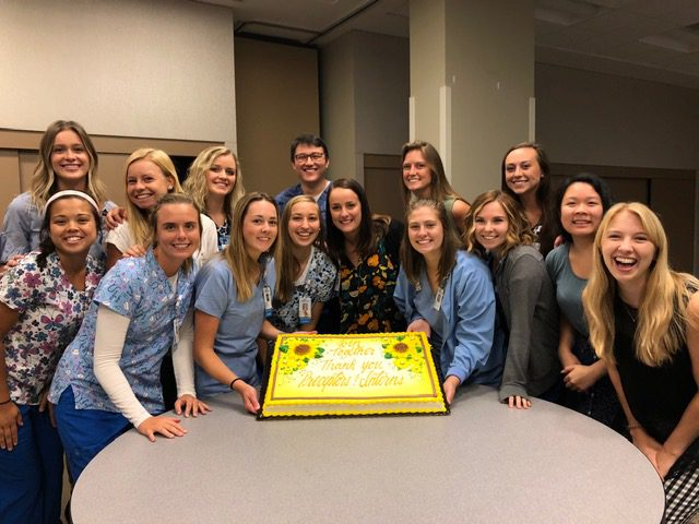 Student nurse interns pose around a cake at the end of their 2019 internship.