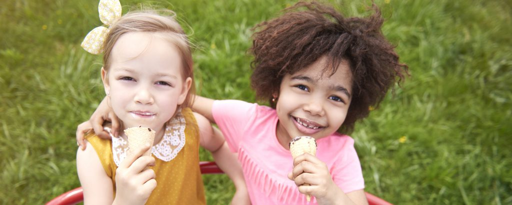 two young girls outdoors eating ice cream cones, on playground, smiling.