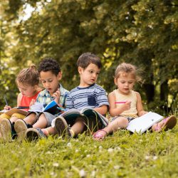 Kids reading in grass