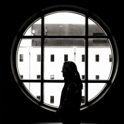 girl silhouetted against round window