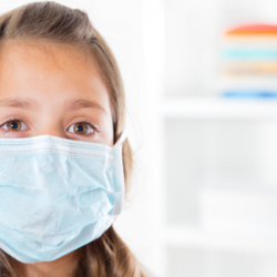 young girl wearing a blue surgical mask