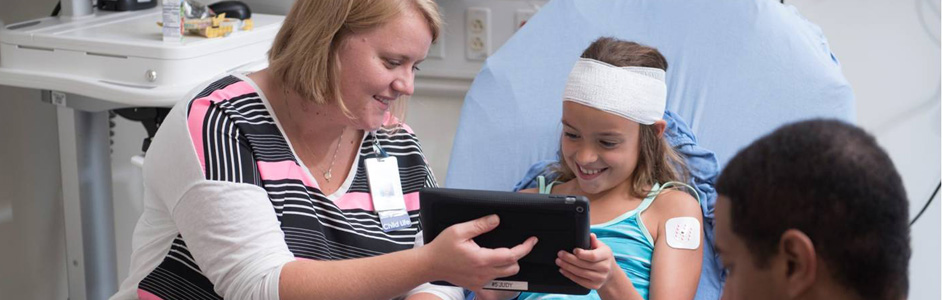 Child Life specialist uses iPad to help distract patient from procedures.