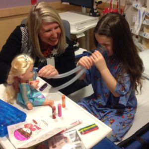 Child life specialist and patient use a doll to learn about procedure.