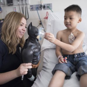 Child life specialist and patient play with Batman doll to learn about procedure.