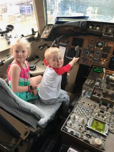 A young blond girl and boy sit in the cockpit of a plane
