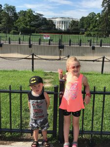 A small boy in a batman hat and a young girl in a pink tank top standing in front of the white house