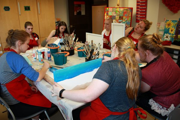 AYA members sitting around a table painting for the AYA paint night