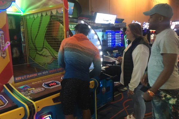 One AYA member plays an arcade basketball game while took other members watch him