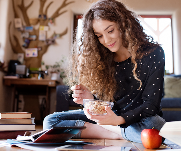 Teenage girl eating fortified cereal and an apple while reading books.