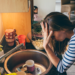 Stressed mom in kitchen that's messy.