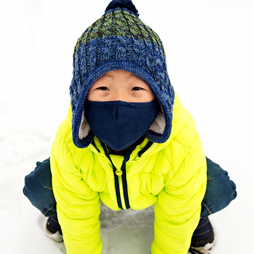Young child outside blowing his nose in the winter.