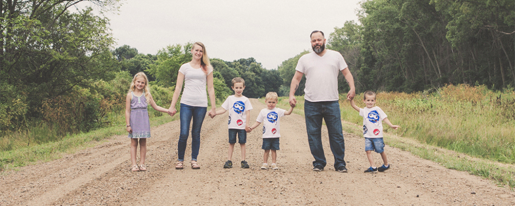 Shelby Herlick's family standing on a dirt road holding hands