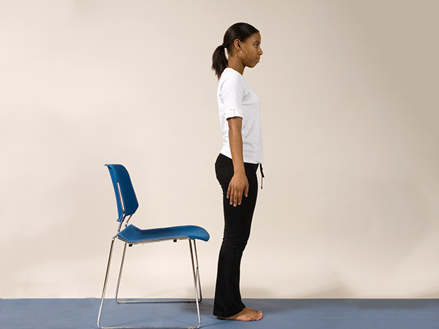 Model demonstrates step 1 of the chair squat exercise